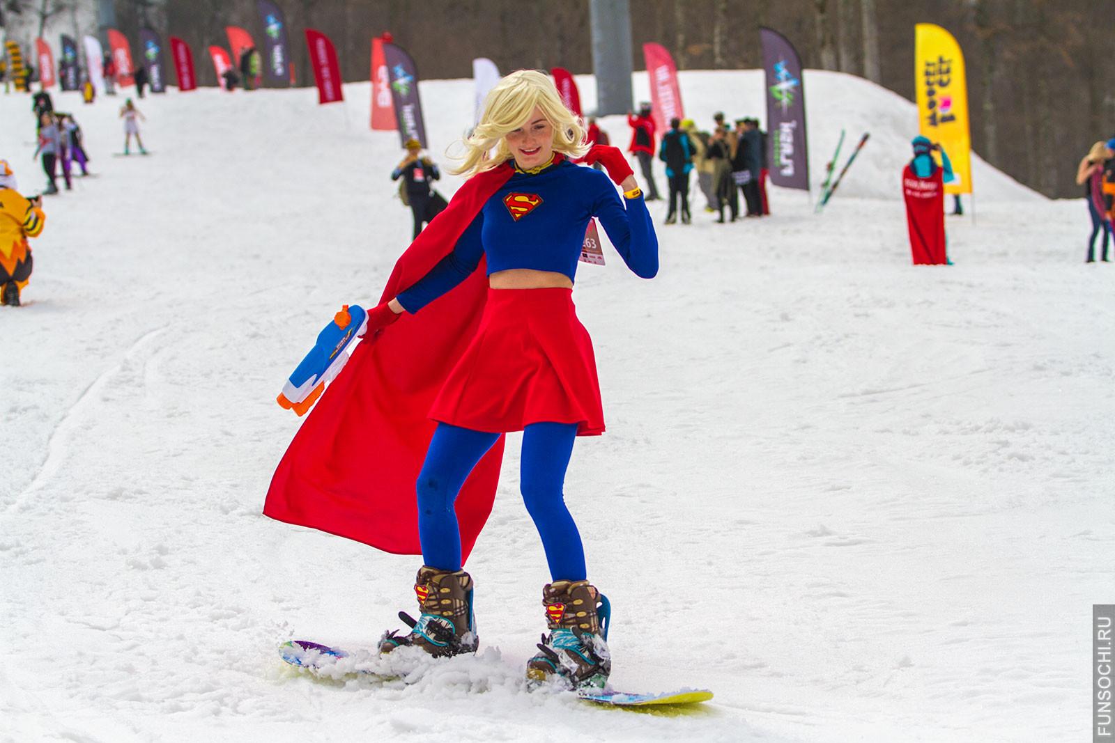 девушка на сноуборде в костюме супервумен