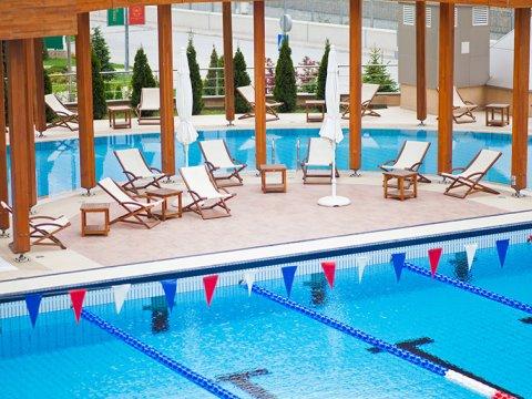 Вид на зону отдыха у открытого бассейнав Гранд Отель Поляна Газпром